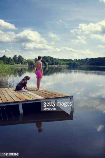 Portrait of teenager standing with labrador retriever on jetty looking over lake on a sunny day