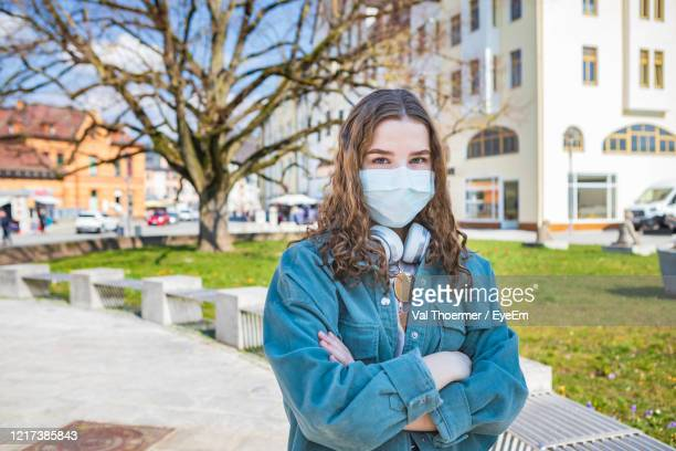 portrait of teenager wearing mask standing in city - val thoermer stock-fotos und bilder