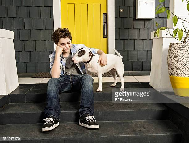 Portrait of teenager (13-15) with dog waiting by door