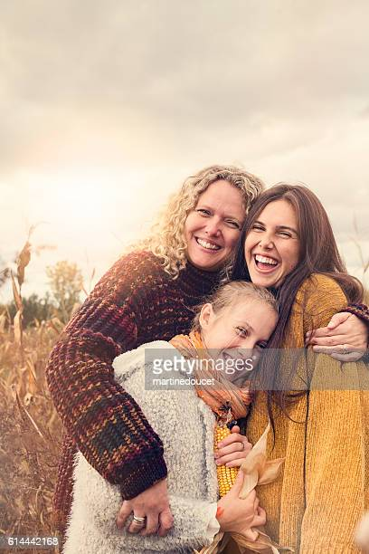 Portrait of teenagers with mother in autumn sunset outdoors.