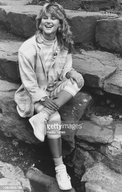 Portrait of television presenter Anthea Turner sitting on stone steps July 31st 1987