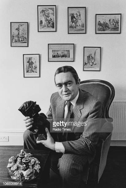 Portrait of television presenter Hugh Scully holding a sculpture photographed for Radio Times in connection with the BBC show 'Antiques Roadshow' 1982