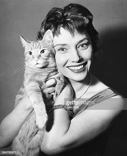 Portrait of television presenter Muriel Young, announcer for ITV, with her pet cat, circa 1955.