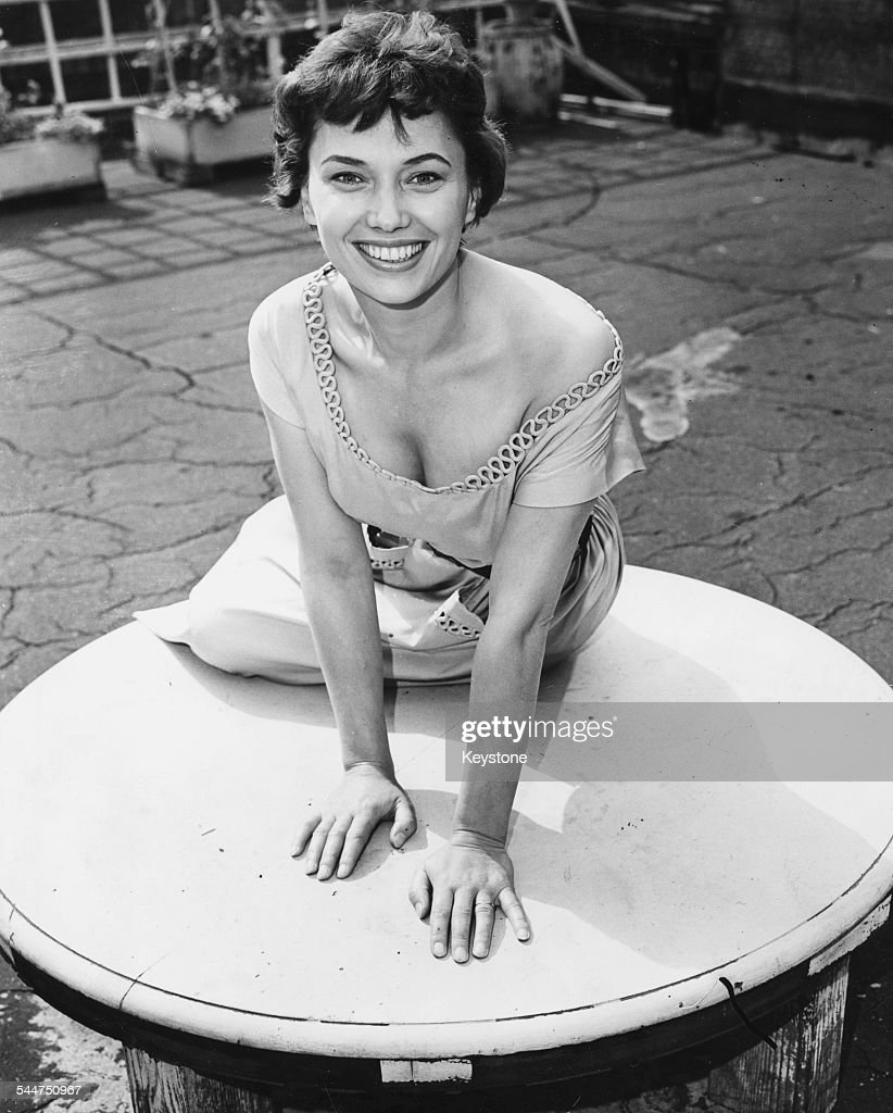 Portrait of television presenter Muriel Young, new announcer for ITV, sitting on top of an outdoor table, London, September 16th 1955.