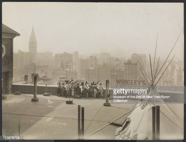 Portrait of ten Native Americans at parapet on the roof of the McAlpin Hotel looking toward the skyline with a tepee on roof in foreground...