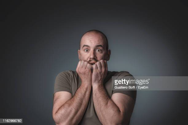 portrait of terrified man standing against gray background - miedo fotografías e imágenes de stock