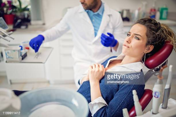 portrait of terrified young girl in the dentist office - dental fear stock pictures, royalty-free photos & images
