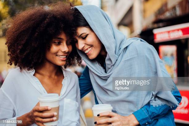 portrait of the afro girl and her arab friend drinking coffee - modest clothing stock pictures, royalty-free photos & images