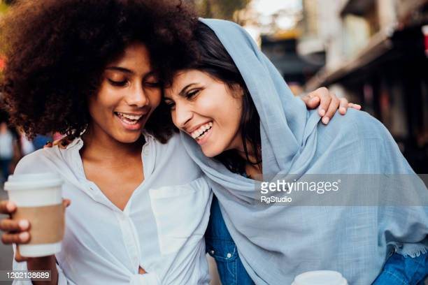 portrait of the afro girl and her arab friend drinking coffee - womens day imagens e fotografias de stock