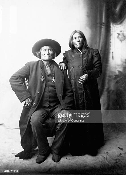 Portrait of the Apache Chief Geronimo and his wive draped in long black jackets