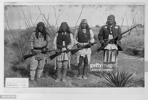 A portrait of the Apache leader Geronimo with his son and two braves holding rifles