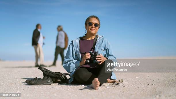 Portrait of the attractive senior African-American woman who sitting on the sand on the beach in front of the group of friends