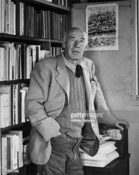 Portrait of the author Henry Miller standing in front of a bookshelf mid twentieth century