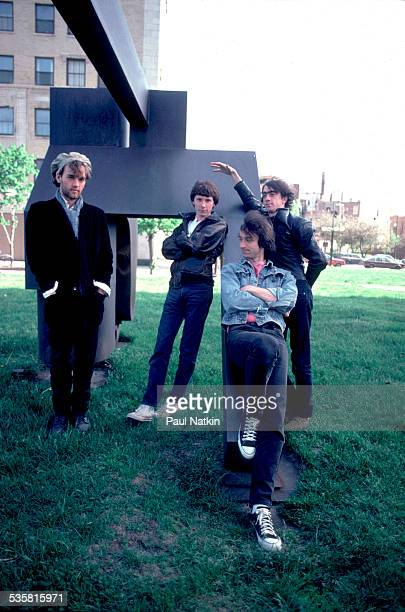 Portrait of the band REM posing outdoors next to a sculpture at Park West Chicago Illinois May 26 1983