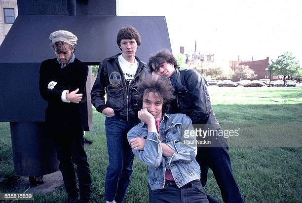 Portrait of the band REM posing outdoors next to a sculpture Chicago Illinois May 26 1983