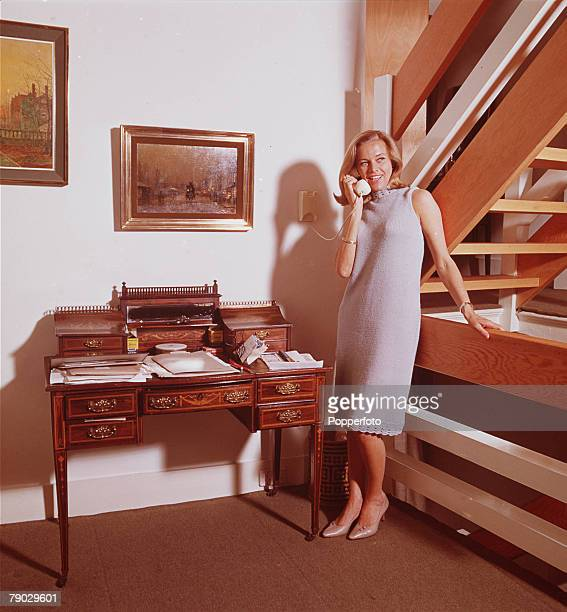 A portrait of the British actress Honor Blackman chatting on the telephone at home smiling