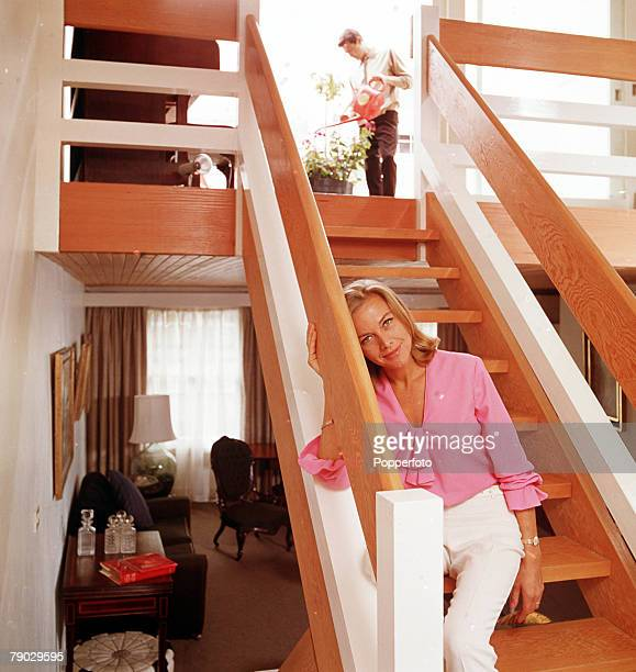 A portrait of the British actress Honor Blackman sitting on the stairs at home smiling at the camera