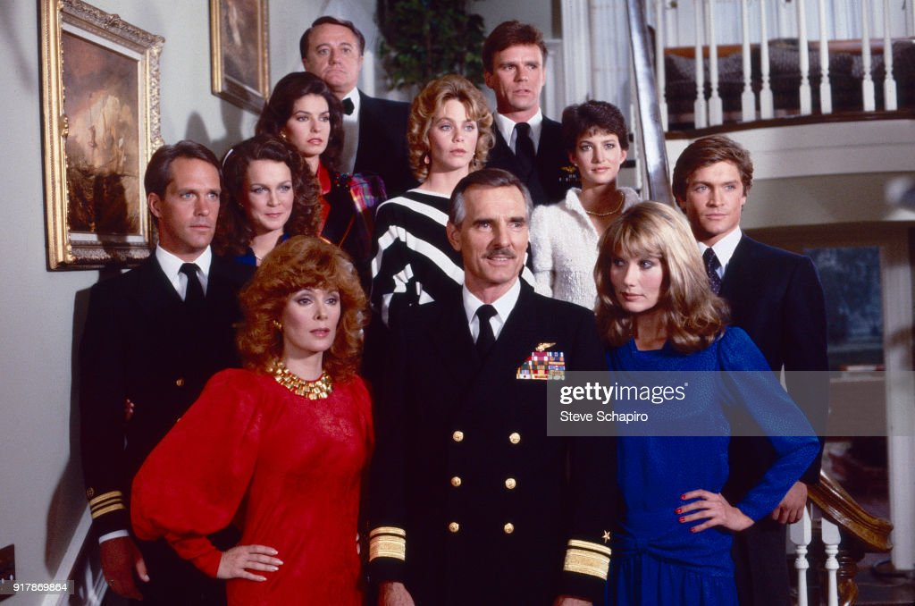 Portrait of the cast of the television series 'Emerald Point NAS' as they pose on a staircase, Los Angeles, California, 1983. Pictured are, fore from left, Jill St John, Dennis Weaver (1924 - 2006), and Maud Adams; second row, from left, Charles Frank, Stephanie Dunham, Susan Dey (in black and white stripes), Doran Clark, and Andrew Stevens; rear from left, Sela Ward, Robert Vaughn (1932 - 2016), and Richard Dean Anderson.