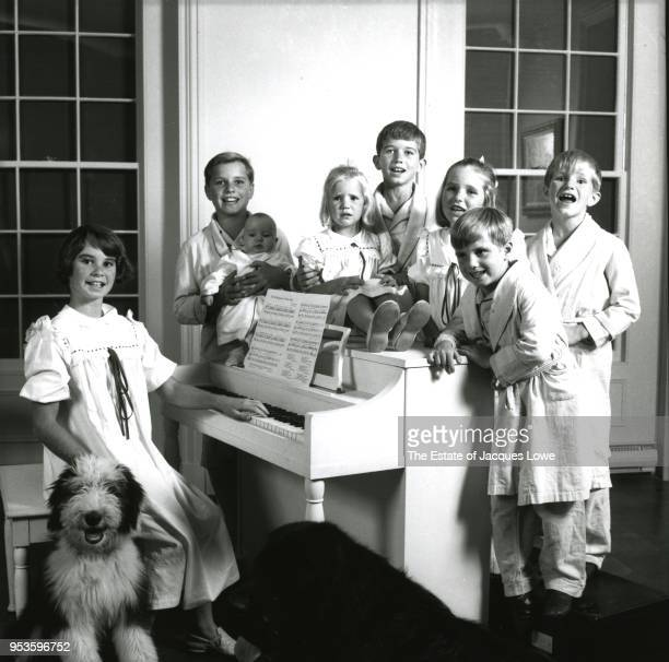 Portrait of the children of Robert and Ethel Kennedy all dressed in pajamas or nighgowns as they pose around a piano late 1963 Pictured are from left...
