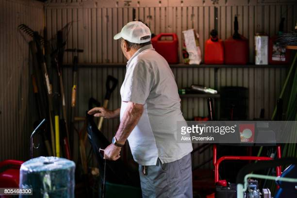 Portrait of the elderly but active senior, 90-years-old man, checking gerdening tools in the farm's shed