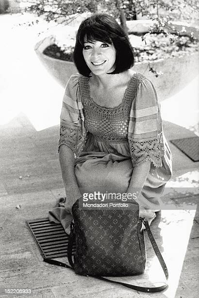 Portrait of the French singer and actress Juliette Greco smiling with a Louis Vuitton handbag Rome 1970s