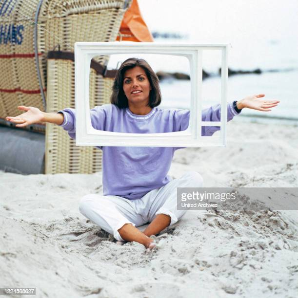 Portrait of the German television presenter Birgit Schrowange posing with a television frame with open hair Germany circa 1989
