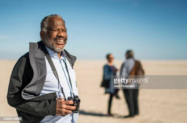 Portrait of the handsome senior African-American man who standing on the beach in front of the group of friends