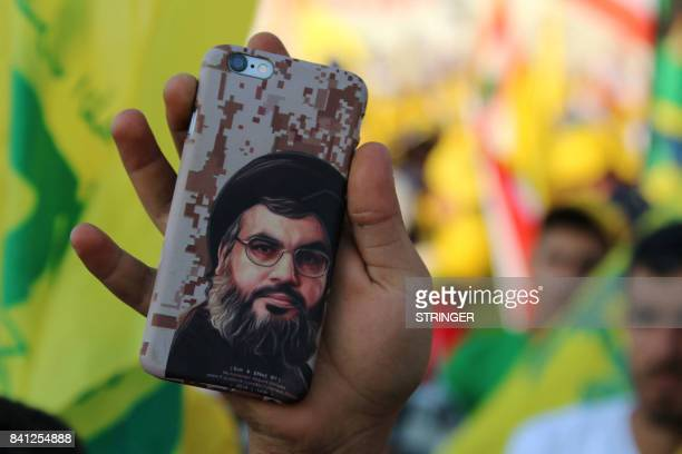 A portrait of the head of the Lebanese Shiite movement Hezbollah Hasan Nasrallah is seen on the back of a mobile phone of a supporter on August 31...
