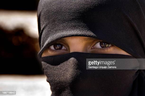 Portrait of the intense gaze of an Arab girl wearing a black veil o niqab, Kahel, Haraz Mountains, Yemen
