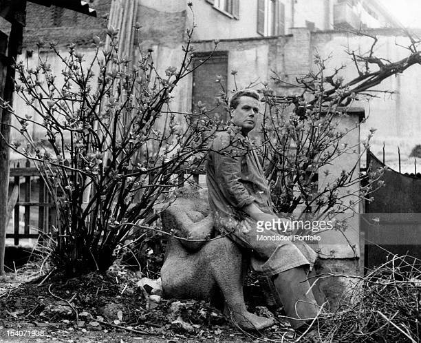 Portrait of the Italian sculptor Luciano Minguzzi in the arms of one of his sculptures in a garden The work represents a female nude Milan April 1958