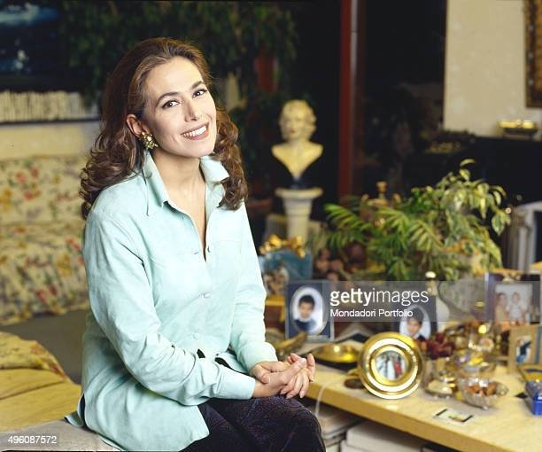 Portrait of the Italian TV presenter and actress Barbara D'Urso sitting smiling at home during a photo shoot Italy 1997