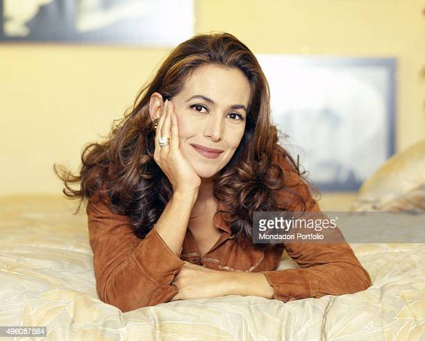 Portrait of the Italian TV presenter and actress Barbara D'Urso lying on her bed during a photo shoot Italy 1997