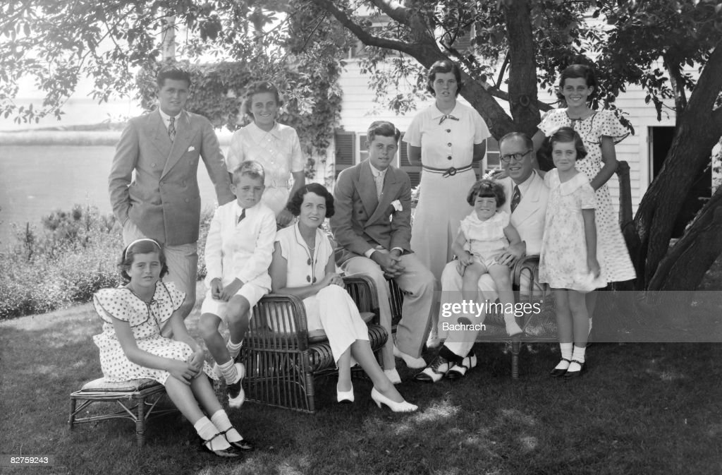 A portrait of the Kennedy family as they sit in the shade of some trees, Hyannis, Massachussetts, 1930s. Seated from left are: Patricia Kennedy (1926 - 2006), Robert Kennedy (1925 - 1968), Rose Kennedy (1890 - 1995), John F Kennedy (1917 - 1963), Joseph P Kennedy Sr (1888 - 1969) with Edward Kennedy on his lap; standing from left are: Joseph P Kennedy Jr (1915 - 1944), Kathleen Kennedy (1920 - 1948), Rosemary Kennedy (1918 - 2005), Eunice Kennedy (rear, in polka dots), and Jean Kennedy.