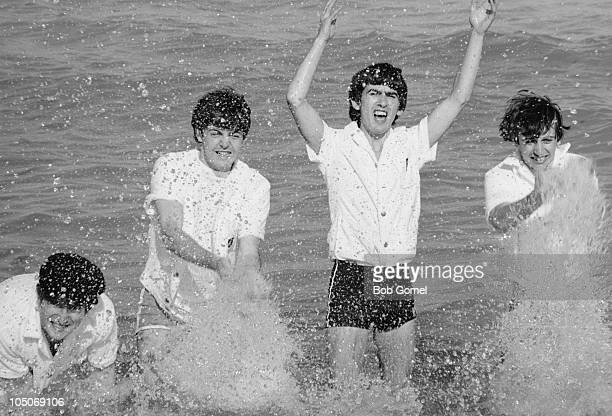 Portrait of the members of the British pop group The Beatles as they splash in the ocean. Miami Beach, Florida, February 16, 1964. Pictured are, from...