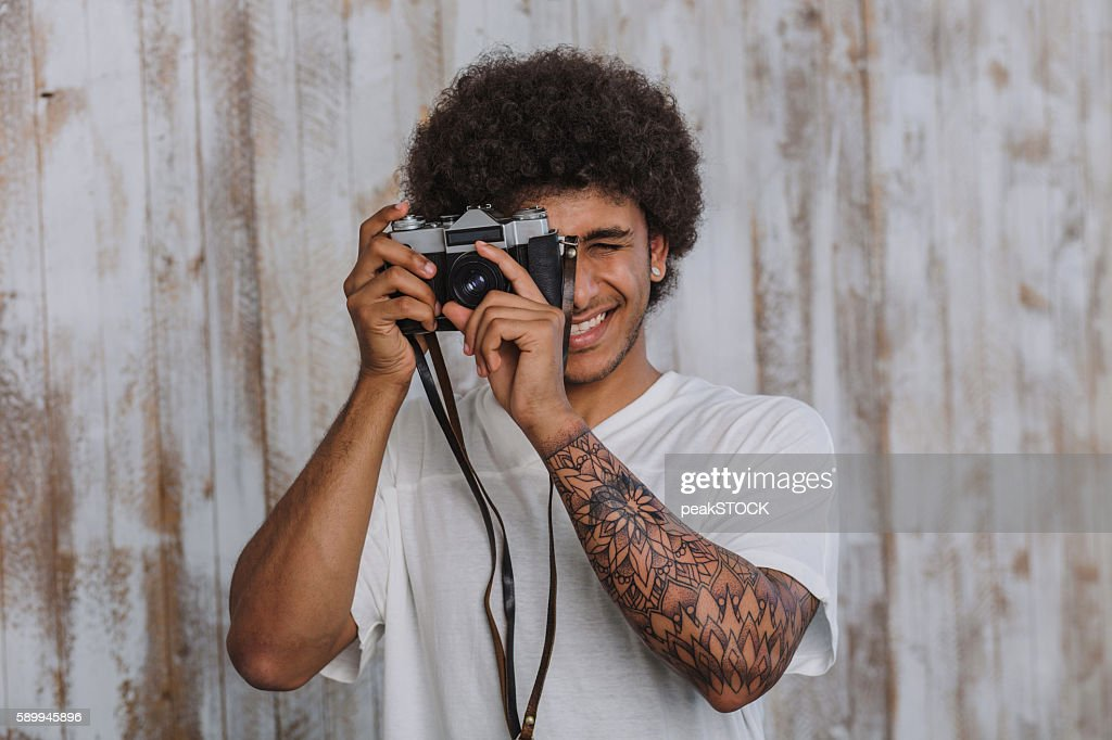 Portrait of the positive curly and Arab male photographer : Stock Photo