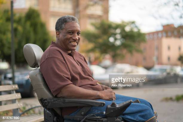 Portrait of the positive, optimistic disabled Black man, paralized veteran who sitting in wheelchair