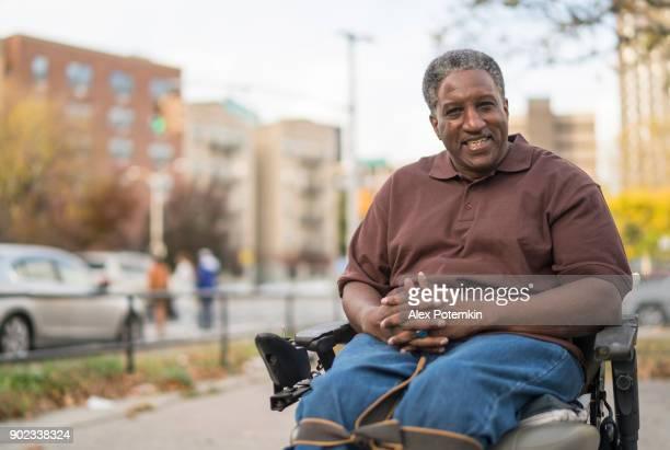 肯定的、楽観的なの肖像画の黒人男性を無効に、車椅子に座っている人のベテランが麻痺 - 麻痺 ストックフォトと画像