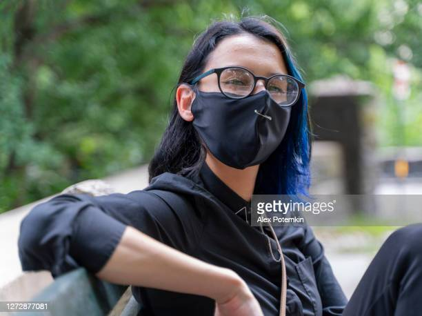 portrait of the pretty smiling 17-years-old teenage girl with the dyed hair wearing eyeglasses and a protective mask. - 16 17 years stock pictures, royalty-free photos & images