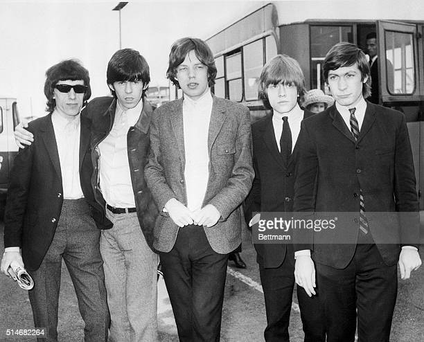 A portrait of The Rolling Stones arminarm at the airport in London England