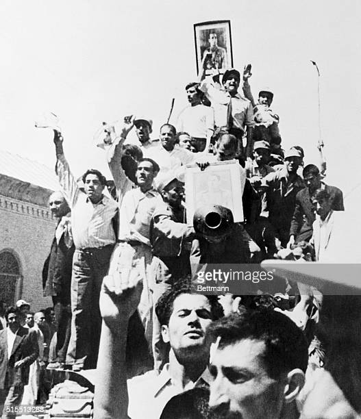 Portrait of the Shah is carried triumphantly atop an Iranian Army tank patrolling the streets of Teheran after the coup that overthrew the regime of...