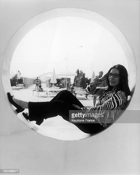 Portrait of the singer Nana MOUSKOURI sitting on a portholestyled windowsill near a beach in Cannes on July 25 1969