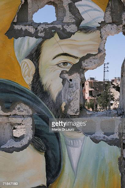 A portrait of the slain Hezbollah leader Abbas Mussawi stands damaged amid the rubble of destroyed buildings after an Israeli bombing campaign July...