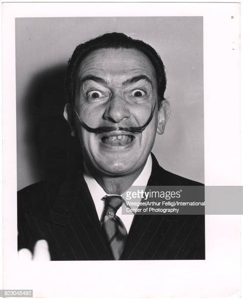Portrait of the Spanish surrealist painter and sculptor Salvador Dali as he makes a comic face, New York, New York, 1940s or 1950s.