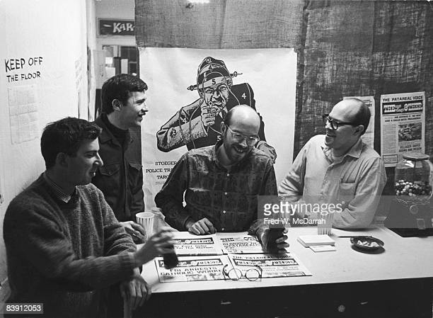 Portrait of the staff of the East Village Other an alternative underground newspaper commonally refered to as EVO gathered around a table upon which...
