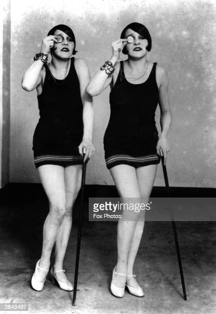 A portrait of the swimsuited Dodge Twin Dancers with their canes and monocles