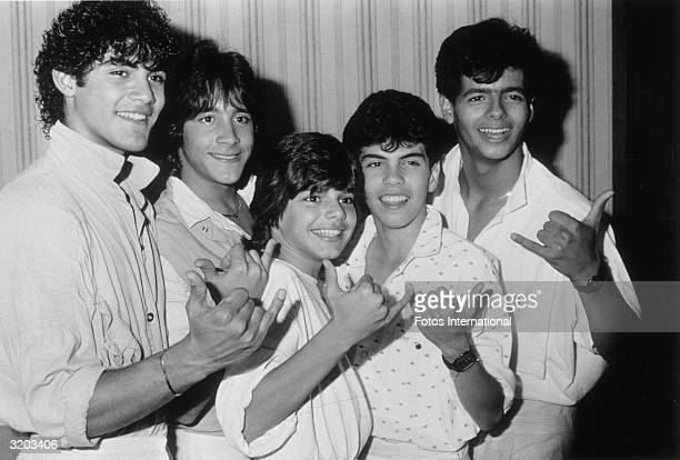 Portrait of the teen pop group Menudo gesturing with their hands while posing in a hallway at the Century Plaza Hotel Los Angeles California