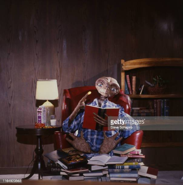 Portrait of the titular puppet from the film 'ET the Extra Terrestrial' seated in an armchair with an open book Los Angeles California 1982 The photo...