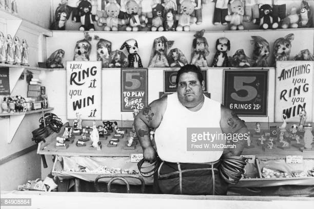 Portrait of the unidentified tatooed operator of a 'ring toss' carnival game at Coney Island Brooklyn New York June 13 1965