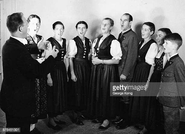 Portrait of the Von Trapp family singing Eleonore Agatha Maria the Baroness Werner Hedwig Martina and Johannes they are conducted by Father Franz...