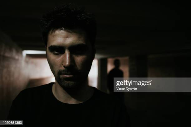 portrait of the young dark haired man in the underground crossing - drug dealer stock pictures, royalty-free photos & images